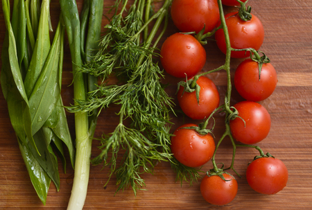 Cherry tomatos, heap of dill, green onion and ramsons on wooden surface Stock Photo