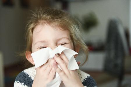 sick petite fille soufflant son nez et couvrant avec mouchoir avec les yeux fermés Banque d'images