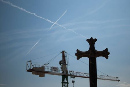 Cross on the roof of Barcelona Cathedral and сonstruction crane against blue sky