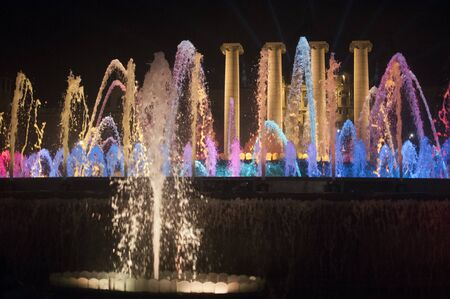 Magic Barcelona fountains, a lot of tourists looking at colorful light show with different water shapes at late evening. Montjuic hill
