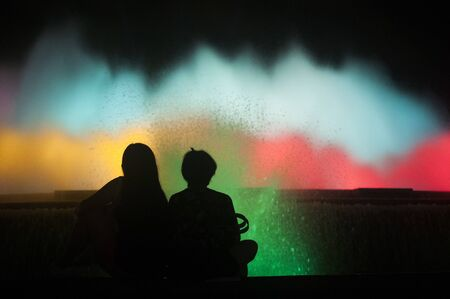 Silhouette of two people watching Magic Barcelona fountains. Lots of tourists looking at colorful light show with different water shapes at late evening
