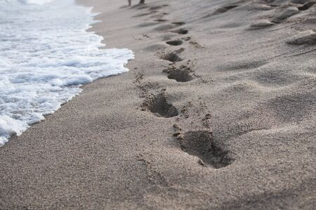 Human footprints in the sand on a coastline
