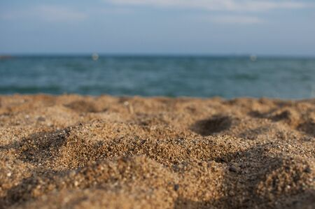 Coastline with the sand in focus and sea and sky in background. Selective focus