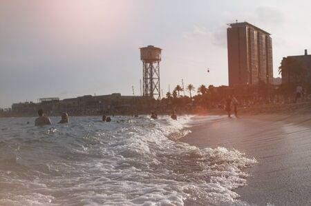 Wave on the sea on Barceloneta beach in Barcelona, Spain with people on the beach in blurred background during sunset Stock fotó