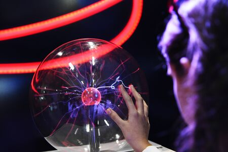 Hand touching with finger electric plasma in glass sphere