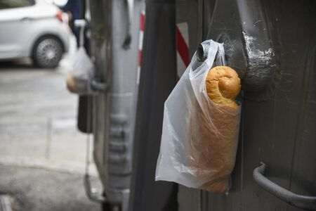 plastic white bag with bread in it, hang on metal container for garbage, left for homeless and hungry people in the city Standard-Bild - 129176162