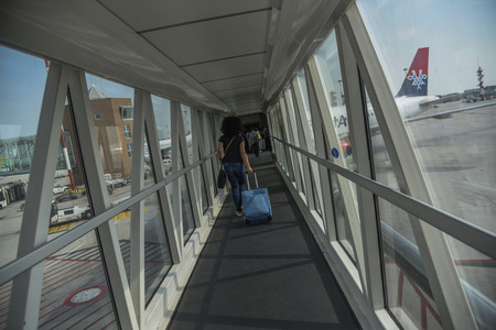 VENICE, ITALY - 01 JUNE 2017: Tourist with carry on luggage walking to airplane of Serbian avia company AirSerbia standing on the airport gate ready to take off