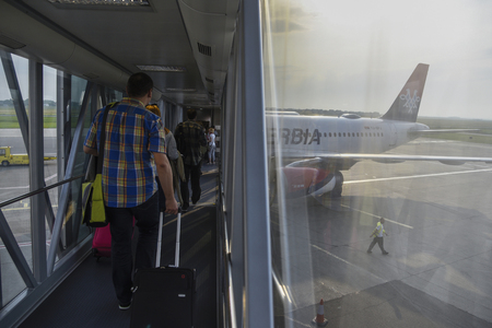 BELGRADE, SERBIA - 01 JUNE 2017: Tourists with carry on luggage walking to airplane of Serbian avia company AirSerbia standing on the airport gate ready to take off Editorial
