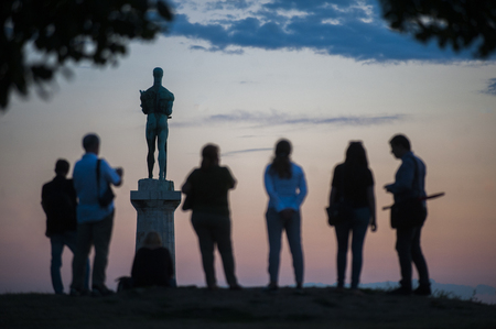 """BELGRADE, SERBIA - AUGUST 18, 2015: Silhouettes of young people during sunset in Kalemedan park with the view of monument """"The Victor"""" at fortress in Belgrade, Serbia"""