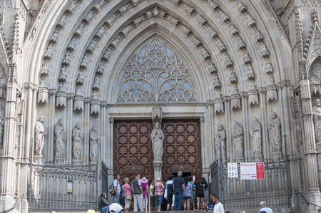 BARCELONA, SPAIN - SEPTEMBER 7, 2014: Tourists entering Cathedral of the Holy Cross and Saint Eulalia in Gothic Quarter, Barcelona, Catalonia, Spain Foto de archivo - 129182995