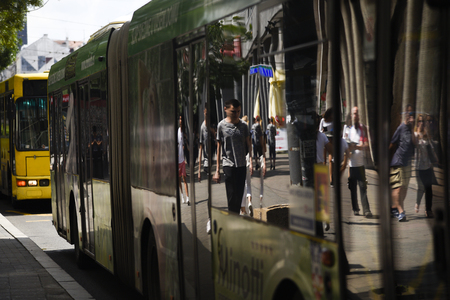 BELGRADE, SERBIA - 24 JUNE 2019: Pedestrian's reflection in the parked bus windows. Every summer Belgrade cuts number of public transport buses Publikacyjne