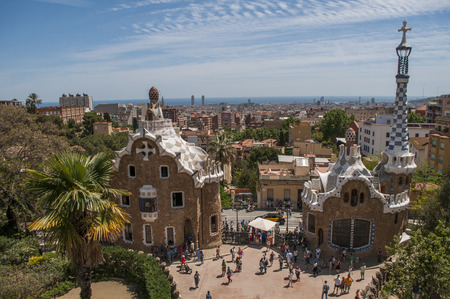 BARCELONA, SPAIN - 7 MAY 2019: View of Barcelona from Park Guell at the middle of a summer day. In the foreground the colourful buildings of the main entrance. Barcelona, Spain.