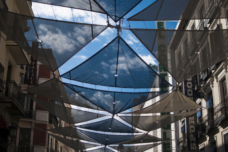 MADRID, SPAIN - SEPTEMBER 14, 2014: Decorative tent to fight the sun on the street in Madrid, Spain Редакционное