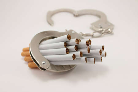 Cigarettes and handcuffs over white background.