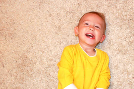 Portrait of a laughing baby lying on a carpet. photo