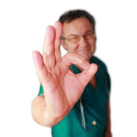 Smiling doctor with okay gesture isolated on white.
