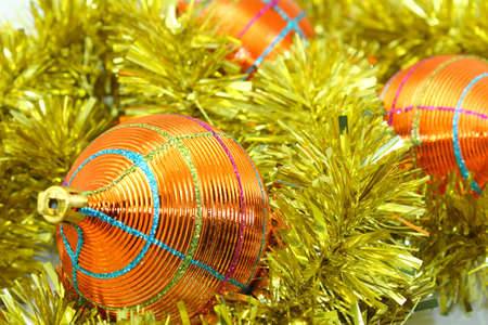 Orange-Yellow Christmas Decorations on Orange-Yellow Tinsel. Stock Photo