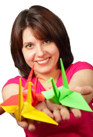 Portrait of a beautiful smiling brunette holding paper crane isolated on white background
