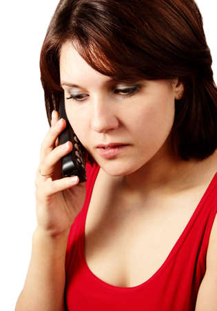 Attractive brunette talking on cell phone and thinking isolated on white background Stock Photo