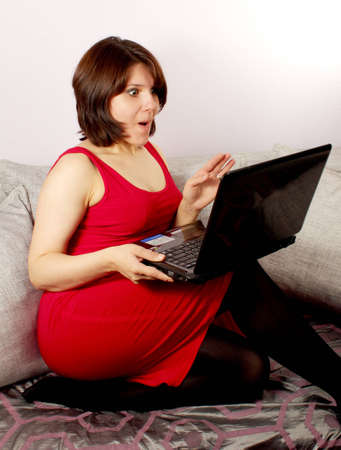 Surprised attractive young women sitting on sofa and using laptop looking on screen Stock Photo