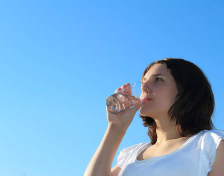 Young woman drinking water on sky background photo