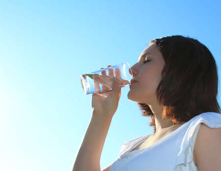 Young woman drinking water on sky background Stock Photo