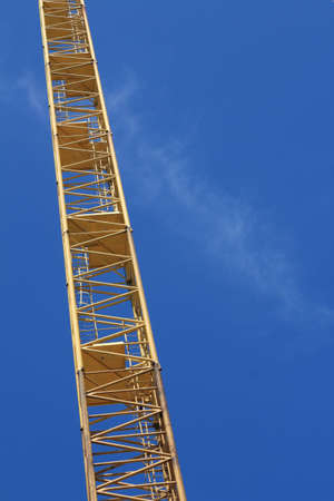 Yellow hoisting crane on blue sky background