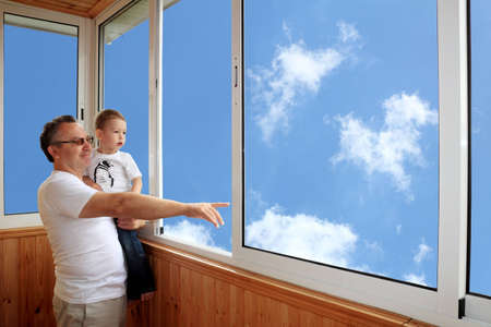 glazing: Grandson and grandfather standing on balcony and looking at the sky