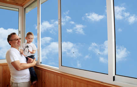 Grandson and grandfather standing on balcony and looking at the sky Stock Photo - 14425962