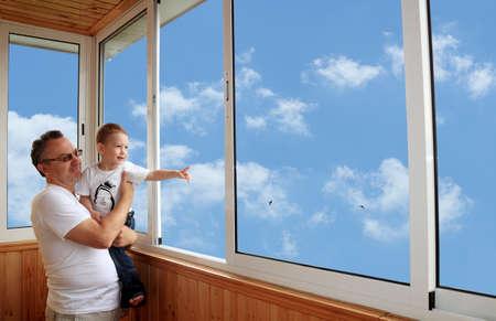 ventana abierta interior: Nieto y abuelo de pie en la terraza y mirando al cielo