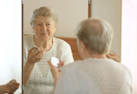 Smiling elderly woman in front of mirror