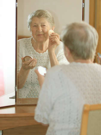 70s adult: Smiling elderly woman in front of mirror