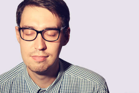 Funny young man wearing glasses with closed eyes