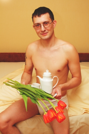 Breakfast in bed. Romantic young man with tray and flowers