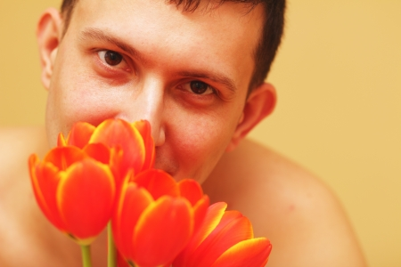 Romantic smiling young man with flowers