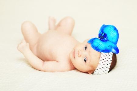 Newborn baby girl with blue flower