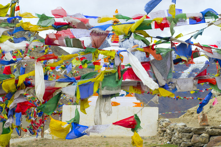 Tibetan multicolored flags surround a white stupa with an ornament in the mountains of the Himalayas. Stock fotó