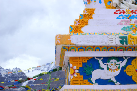 Ornament on a Tibetan stupa in the Himalayan mountains. In the background are snowy mountains and tibetan flags.