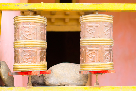 Cylinders with Tibetan symbols for reading mantras. Religion concept.
