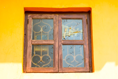 An old broken window is taped up against a yellow wall.