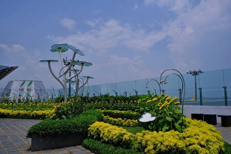 Sunflower Park with large metal flowers surrounded by a glass fence. Ecological concept in the urban environment.