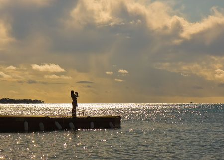 Girl photgraphing by the sea in Backlight Stock Photo - 5113557