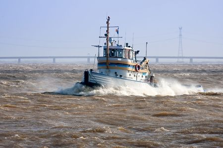Tugboat crossing the storm, at his way to the safe harbor photo