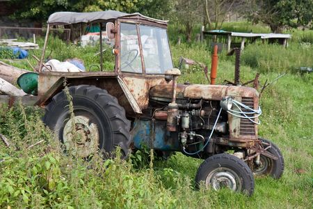 Old neglected tractor between the weed at a farmyard Stock Photo - 5451610