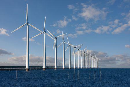 オランダの seabarrier に沿って海に立っている巨大な風車