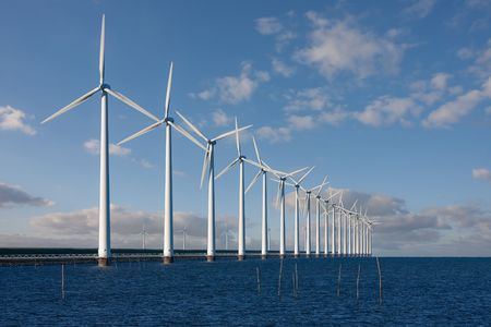 Enormous windmills standing in the sea along a Dutch seabarrier 스톡 콘텐츠
