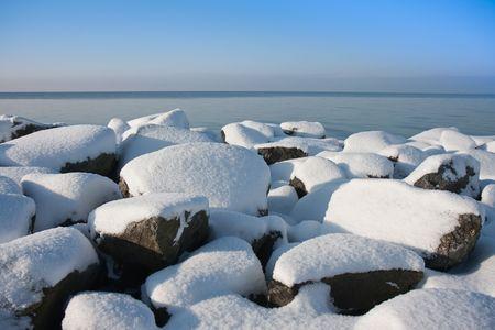 Snowy rocks of Dutch breakwater in wintertime photo