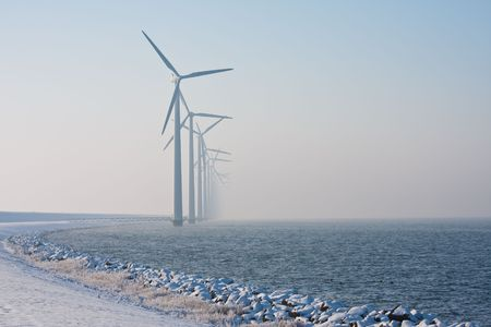 Long row of Dutch windmills disappearing in winter haze photo
