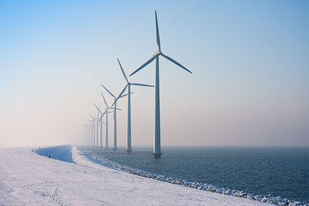 Long row of Dutch windmills disappearing in winter haze