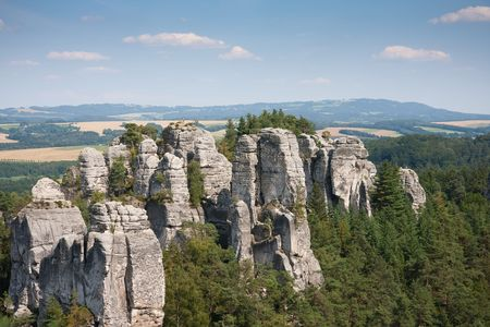 Sandstone pillars arising above the wood in the bohemian paradise of the Czech republic 免版税图像